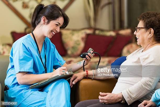 Home healthcare nurse checks patient's blood pressure