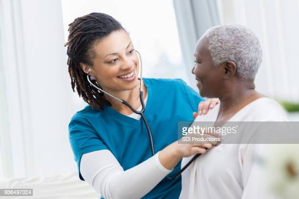 home healthcare nurse checks patient's lungs - lung stock pictures, royalty-free photos & images