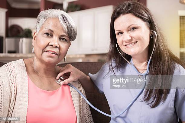 home healthcare nurse conducts physical exam with senior adult woman. - house call stock photos and pictures