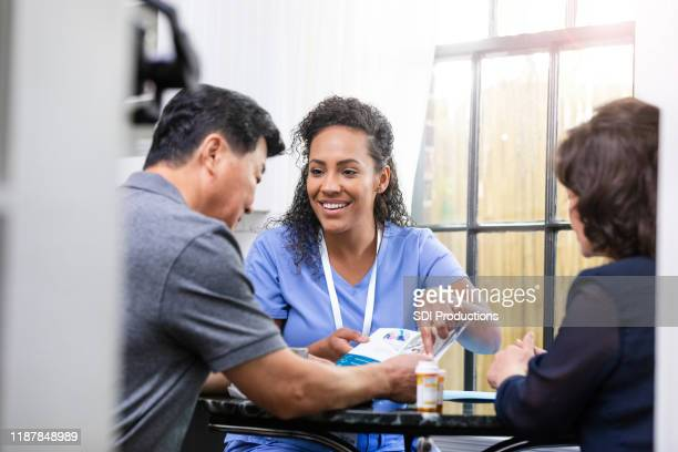 home healthcare nurse discusses care with patient - flyer leaflet stock pictures, royalty-free photos & images
