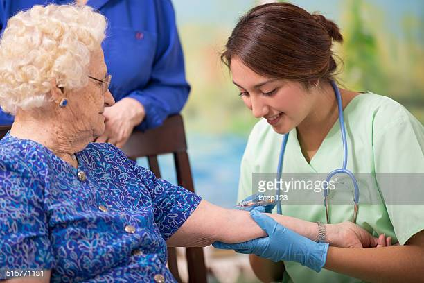 home healthcare nurse giving injection to elderly woman. - besmettelijke ziekte stockfoto's en -beelden