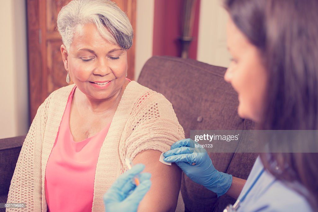 Home healthcare nurse giving injection to senior adult woman. : Stock Photo