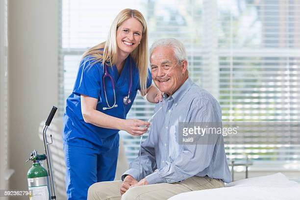 Home healthcare nurse helping elderly man with oxygen