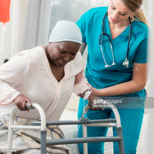 home healthcare nurse helps woman stand up - hospice stock pictures, royalty-free photos & images