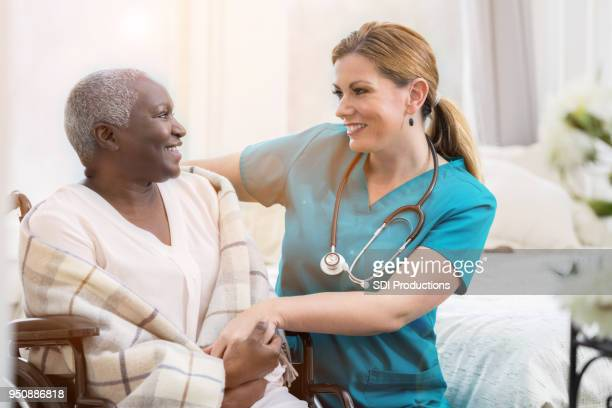 Home healthcare nurse smiles while checking on senior patient