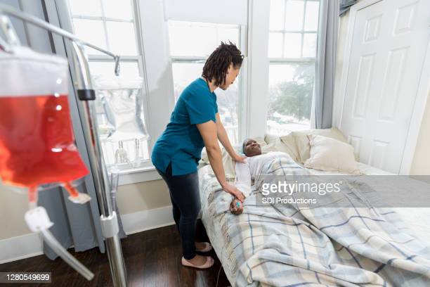 home healthcare nurse visits with ill patient - hospice stock pictures, royalty-free photos & images