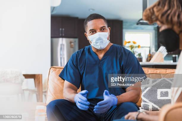 home healthcare nurse visits with patient during   covid-19 - male animal stock pictures, royalty-free photos & images