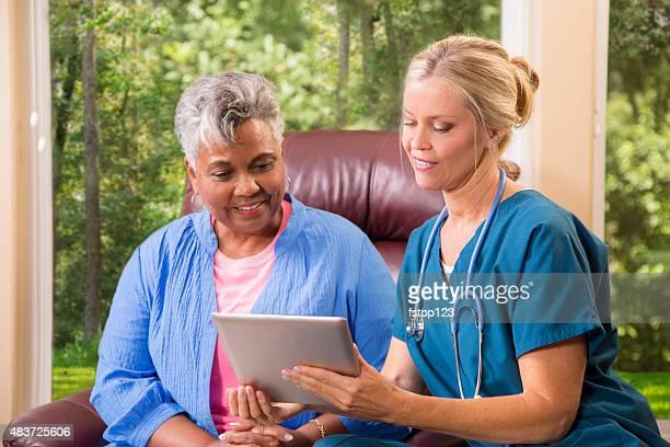 Home healthcare nurse with senior adult patient. Digital tablet.