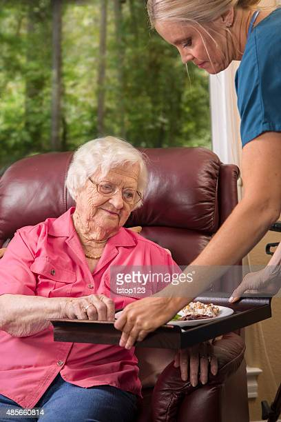 home healthcare nurse with senior adult patient. meal. - meals on wheels stock pictures, royalty-free photos & images