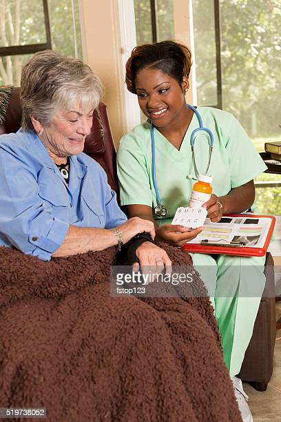 Home healthcare nurse with senior adult patient. Medications.