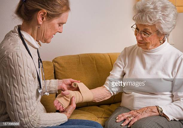 home healthcare nurse wraps bandage on wrist of senior woman - elastic bandage stock photos and pictures