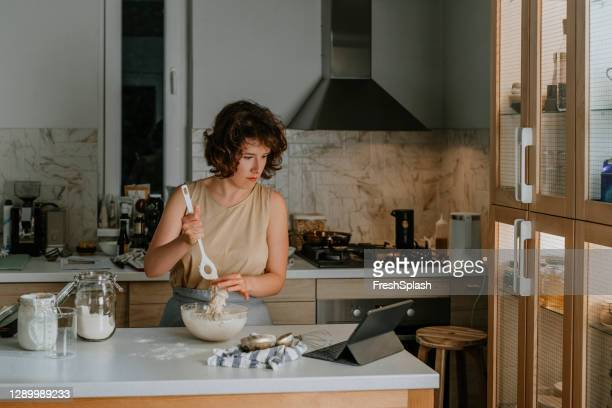 home hobbies: a woman baking sourdough bread from scratch by following an online video recipe on her tablet - following stock pictures, royalty-free photos & images