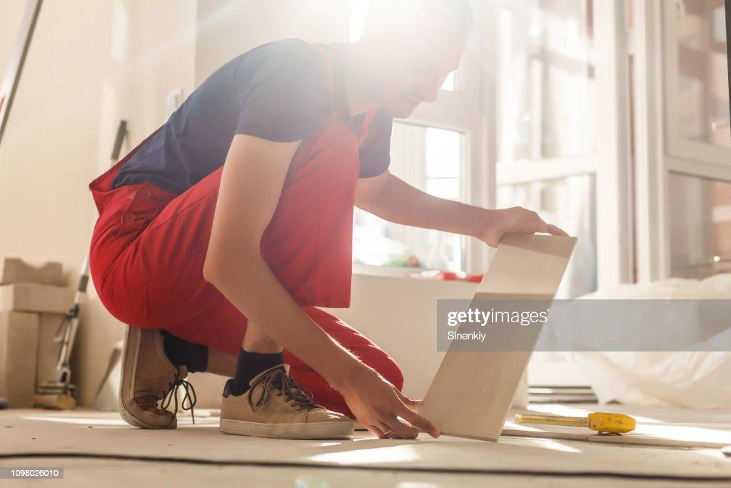 Home improvement, renovation - construction worker tiler is tiling, ceramic tile floor adhesive : Foto de stock