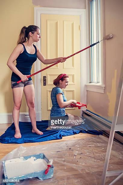Renovierung, zwei junge Frauen, die Gemälde an den Wänden.