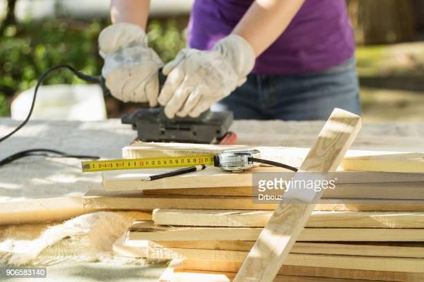 DIY - Home improvement; woman sanding wood plank