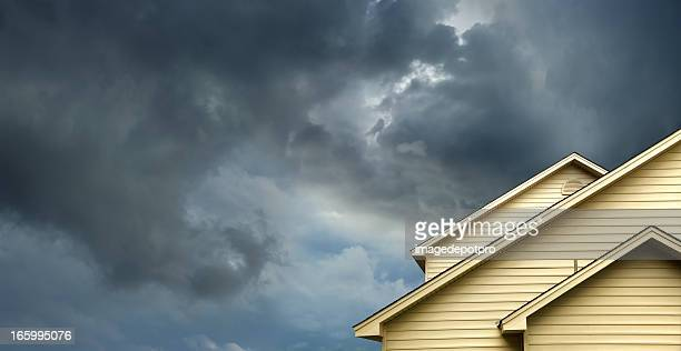 home in stormy day - roof stock photos and pictures