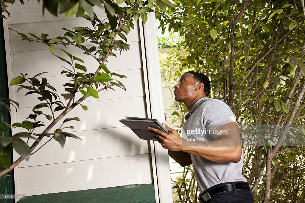 Home inspection on exterior.  Using digital tablet to record results : Stock Photo