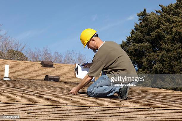 home inspector checking the roof of a house. - roof stock photos and pictures