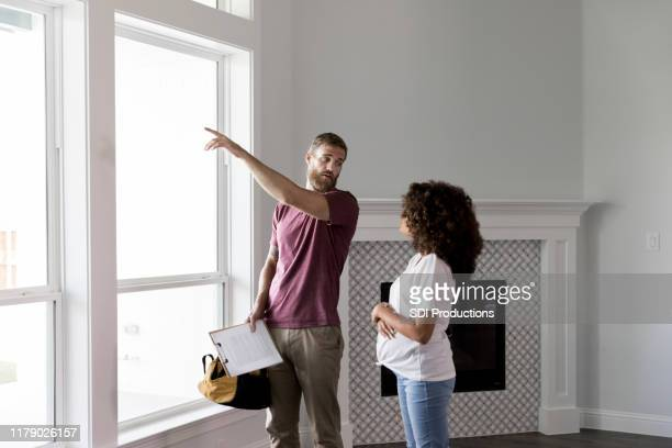 home inspector points to something outside while talking with homeowner - inspector stock pictures, royalty-free photos & images