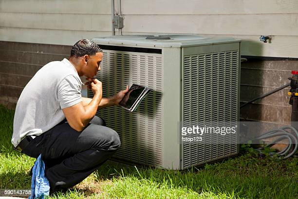 Home inspector, repairman uses digital tablet to check air conditioners.
