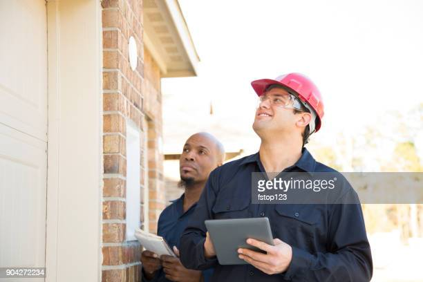 Home inspectors examine recent construction using digital tablet.