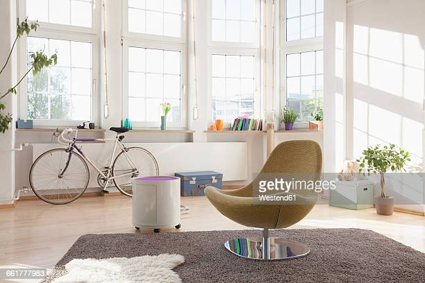 home interior with bicycle and chair - sessel stock-fotos und bilder