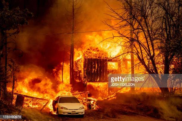 Home is engulfed in flames as the Dixie fire rages on in Greenville, California on August 5, 2021. - The largest wildfire in California has razed a...