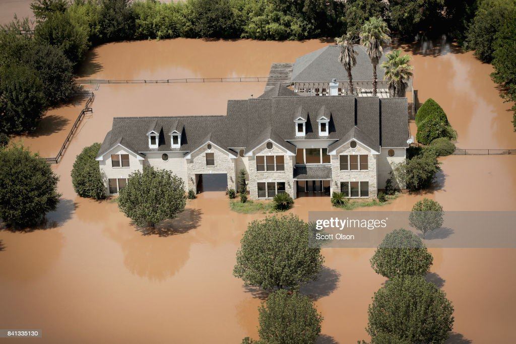 A home is surrounded by floodwater after torrential rains pounded Southeast Texas following Hurricane and Tropical Storm Harvey on August 31, 2017 near Sugar Land, Texas. Harvey, which made landfall north of Corpus Christi August 25, has dumped nearly 50 inches of rain in and around areas Houston.