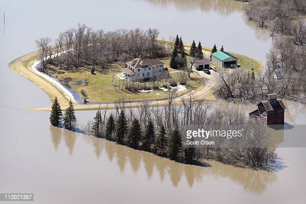A home is surrounded by floodwater from the Red River on April 11 2011 near Fargo North Dakota Although the Red River crested in Fargo on Saturday at...