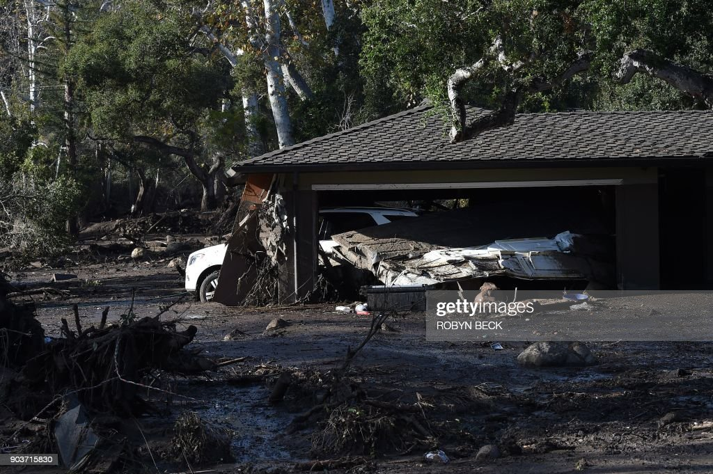 TOPSHOT - A home is surrounded by mud and debris caused by a massive mudflow in Montecito, California, January 10, 2018. Search and rescue efforts intensified January 10 for hundreds of Montecito residents feared trapped in their homes after deadly walls of mud and debris roared down California hillsides stripped of vegetation by recent, ferocious wildfires. / AFP PHOTO / Robyn Beck