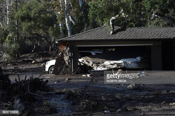 TOPSHOT A home is surrounded by mud and debris caused by a massive mudflow in Montecito California January 10 2018 Search and rescue efforts...