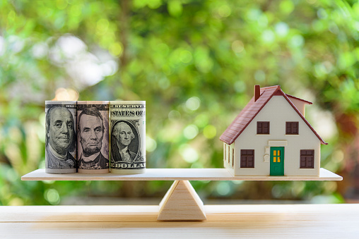 Home loan / reverse mortgage or transforming assets into cash concept : House model, US dollar notes on a simple balance scale, depicts a homeowner or a borrower turns properties / residence into cash 1024531896
