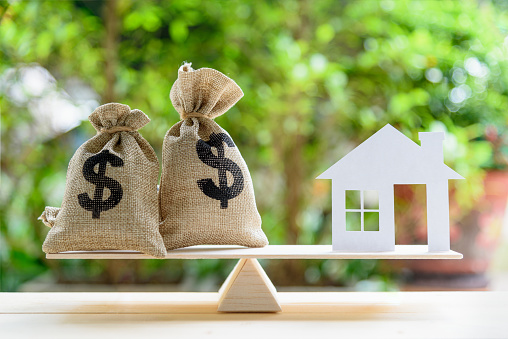 Home loan / reverse mortgage or transforming assets into cash concept : House paper model , US dollar hessian bags on a wood balance scale, depicts a homeowner or a borrower turns properties into cash 1025416706