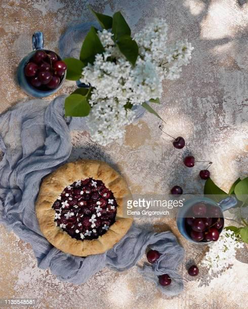 home made galette with cherry and spring flowers - elena blume stock-fotos und bilder