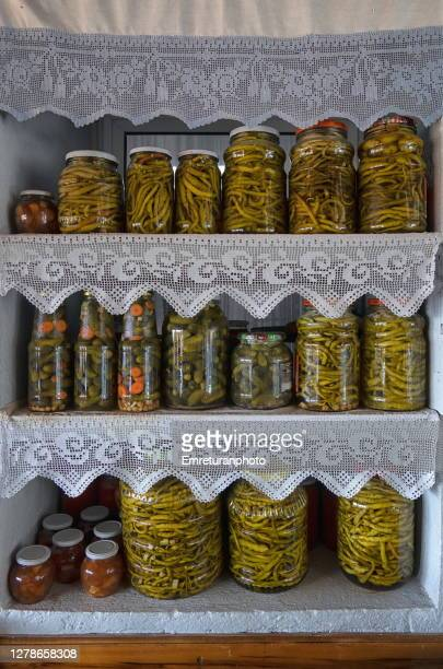 home made pickles and tomato paste in glass jars exhibited on shelves. - emreturanphoto - fotografias e filmes do acervo