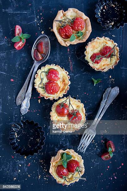 home made tarteletts with cherry tomatoes on black