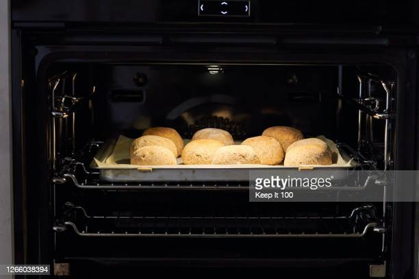home made wholemeal rolls baking in the oven - butter stock pictures, royalty-free photos & images