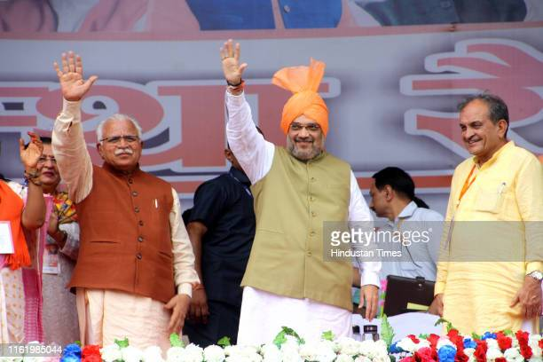 Home Minister Amit Shah Haryana Chief Minister Manohar Lal Khattar and BJP MP Birender Singh waves at people during Aastha Rally on August 16 2019 in...