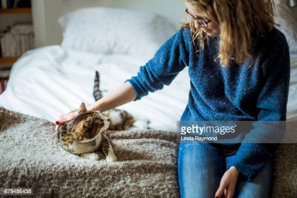 Home Moments - A girl and her cat sitting on a bed and looking at each other