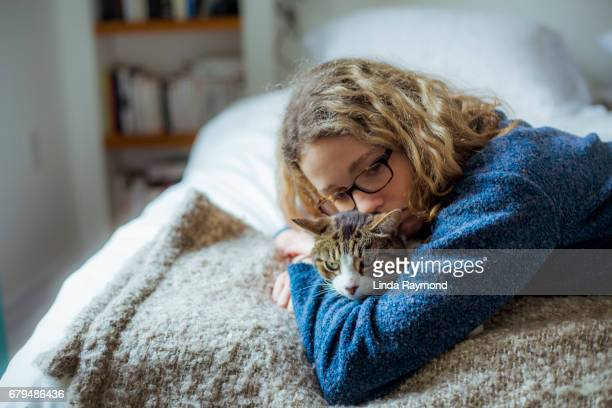 Home Moments - A girl hugging her tabby cat on a bed