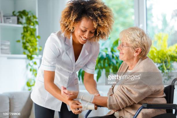 home nurse bandaging the wrist an elderly lady - bandage stock pictures, royalty-free photos & images
