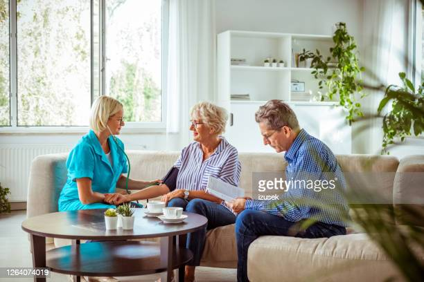 home nurse checking the blood pressure of the elderly lady - blood vessel stock pictures, royalty-free photos & images