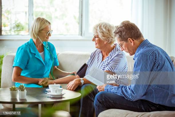 home nurse checking the blood pressure of the elderly lady - artery stock pictures, royalty-free photos & images
