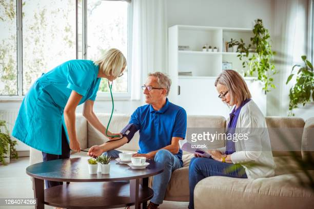 home nurse checking the blood pressure of the elderly man - artery stock pictures, royalty-free photos & images