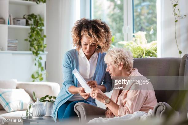 home nurse taking care of senior woman - home carer stock photos and pictures