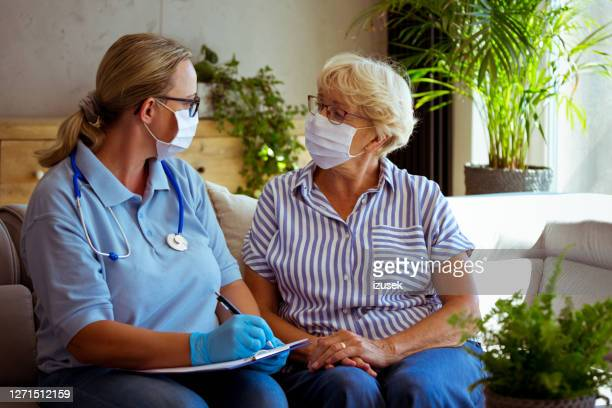home nurse visiting senior woman during quarantine - izusek stock pictures, royalty-free photos & images