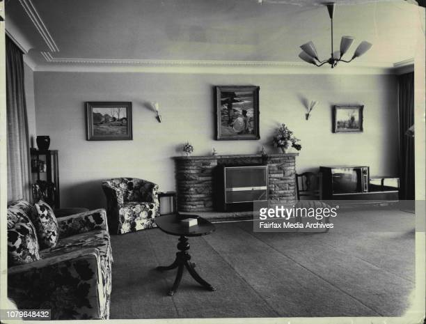 Home of Mr Justice and Mrs HerronA corner of the drawingroom showing the curved sandstone mantelpiece with Hanke's oil The Morning Dip above it...