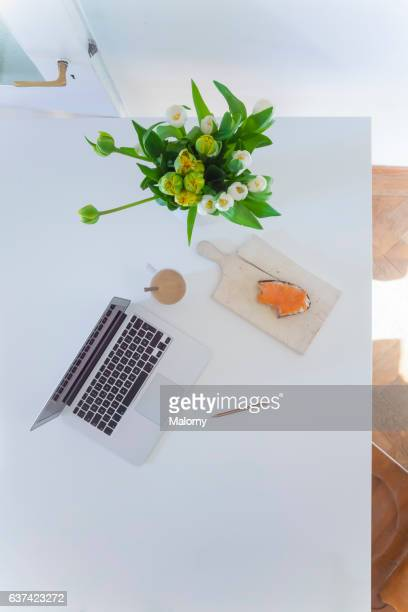 Home office: High angle view or directly above view of laptop with food, coffee and flower vase on white table