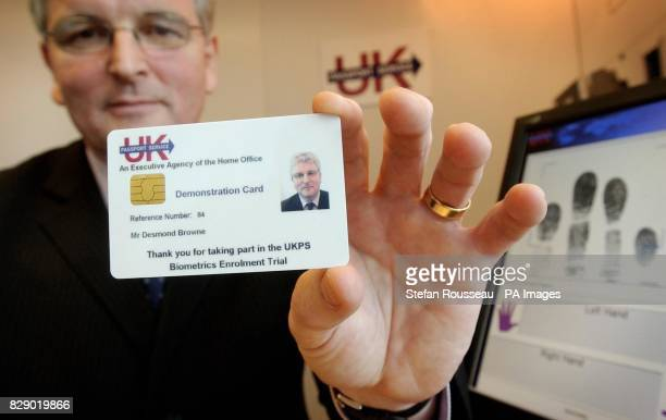 Home Office Immigration Minister Des Brown holds one of the new biometric identification cards on Thursday the technology for which will begin...