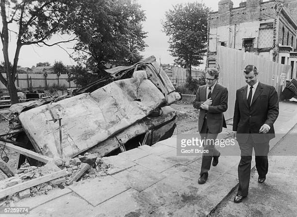Home Office official Robert Morris and Malcolm Ferguson in charge of community relations at Scotland Yard touring the scene of rioting in Brixton...
